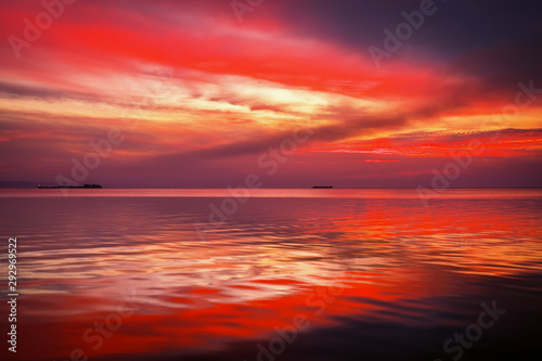 Wall Murals Magenta Fiery dramatic landscape with the sea, beautiful sky and ships. Dawn. small waves, almost calm.