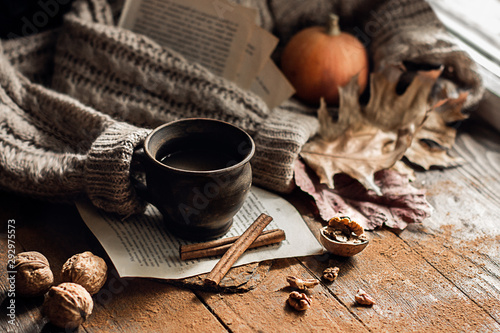 Obraz na plátně  Autumn, fall leaves, a hot steaming cup of coffee and a warm sweater on a wooden table background