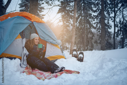 Obraz na plátně Confident solo woman traveller camping through an evergreen winter forest in Can