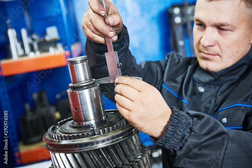 Fototapeta Truck repair service. serviceman measuring gear shaft of gearbox obraz