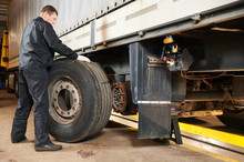 Truck Repair Service. Mechanic Works With Tire In Truck Workshop