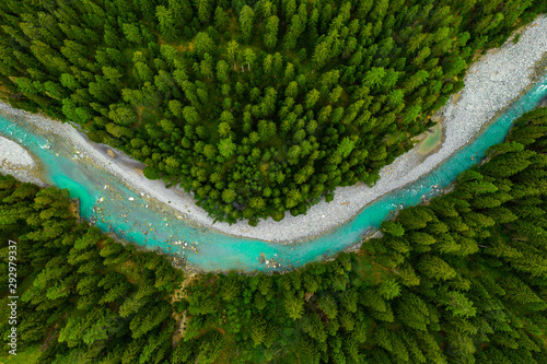 Fototapeta Inn River flowing in the forest in Switzerland. Aerial view from drone on a blue river in the mountains obraz