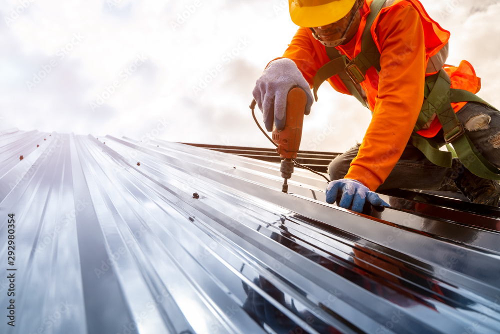 Fototapety, obrazy: Construction worker install new roof,Roofing tools,Electric drill used on new roofs with Metal Sheet.
