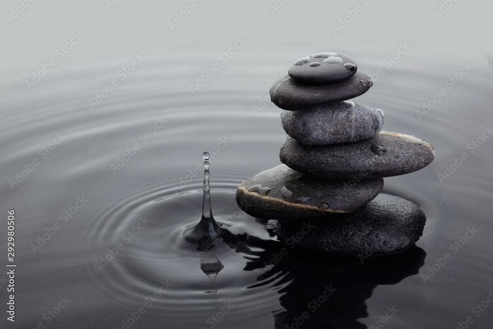 Fototapeta Zen stones in balanced pile in water on rippled water surface and water drop.