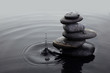 canvas print picture - Zen stones in balanced pile in water on rippled water surface and water drop.