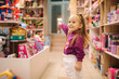 canvas print picture - Adorable little girl shopping for toys. Cute female in toy store. Happy young girl selecting toy