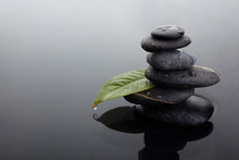 Zen Stones In Balanced Pile And Green Leaf With Water Drops In Water