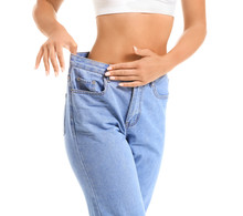 Beautiful Young Woman In Loose Jeans On White Background. Weight Loss Concept