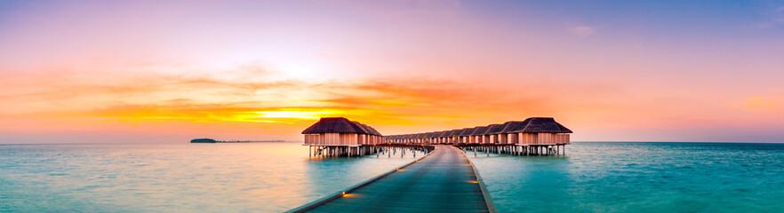 Nevjerojatna panorama zalaska sunca na Maldivima. Luksuzne odmarališne vile s pogledom na more s mekim led svjetlima pod šarenim nebom. Prekrasno sumračno nebo i šareni oblaci. Prekrasna pozadina plaže za odmor