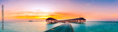 Deurstickers Lichtroze Amazing sunset panorama at Maldives. Luxury resort villas seascape with soft led lights under colorful sky. Beautiful twilight sky and colorful clouds. Beautiful beach background for vacation holiday