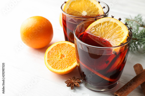 Recess Fitting Tea Glasses of tasty mulled wine with orange on white wooden background, close up