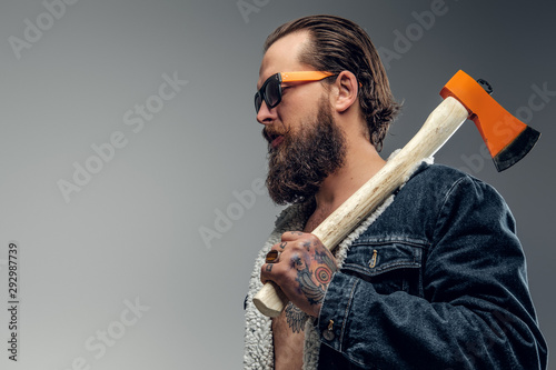 Fotomural  Brutal bearded man in sunglasses and denim jacket is holding axe.