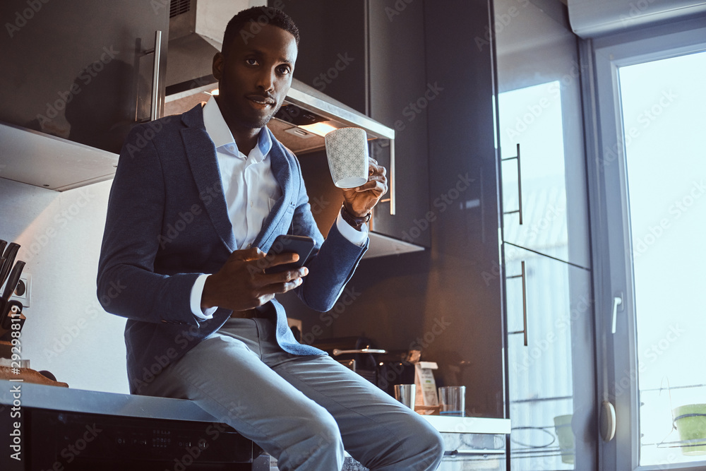 Fototapeta Groomed african businessman is enjoying his morning coffee while chatting by mobile phone at his kitchen.
