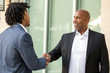 Mature African American casually dressed businessman shaking hands.