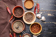 Bowls with different dry herbs and spices on wooden background
