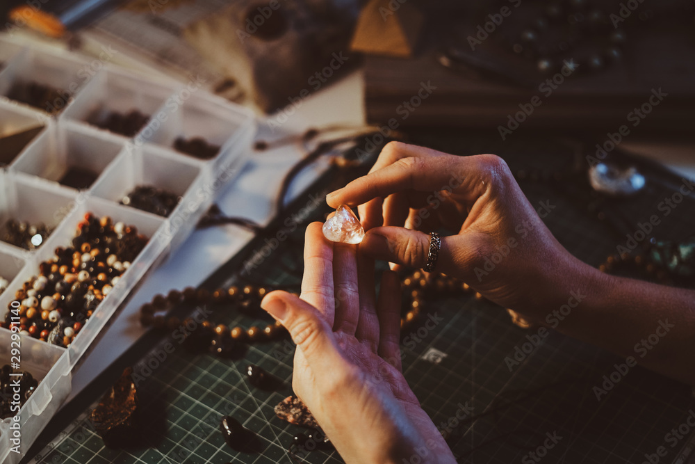 Fototapeta Young woman is holding semi precious stone in hands, close up photoshoot.