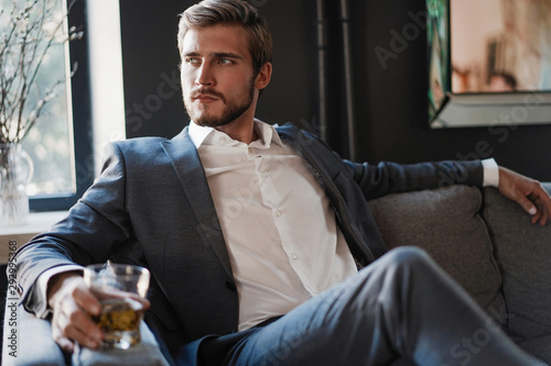 Fototapeta Handsome and successful businessman in stylish suit holding glass whiskey while sitting at office. obraz