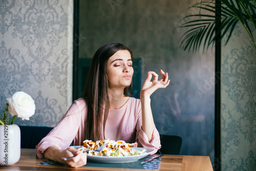 Canvas Print young lady sitting in a beautiful restaurant, enjoying lunch
