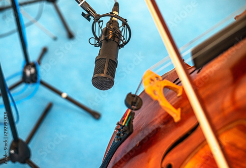 Closeup of a professional microphone recording cello playing at the studio. - 292995928