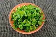 Bowl Of Freshly Rinsed Raw Shredded Bok Choy In Orange Bowl On Burlap