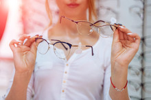 Modern Eyeglasses In Woman's Hands. Eye Care And The Choice The Means To Improve Vision. Macro Shot.