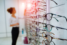 Eyeglasses Shop. Woman Trying On Glasses In Optical Store