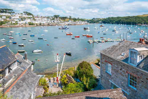 View of beautiful Cornish harbour town Fowey and boats moored in Fowey Estuary from Polruan, South Cornwall, UK