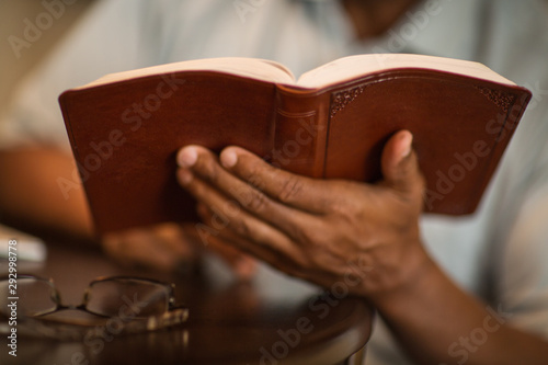 African American man praying and reading the Bible. Wallpaper Mural