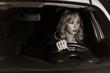 Noir film. Young confident businesswoman driving car. City concept....