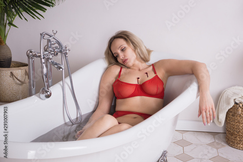 Fotografie, Obraz Lifeless beautiful woman lies in a bathtub
