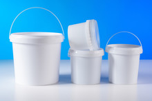 Plastic Buckets. Jar With A Handle For Storing Food. Container For Food Production. Plastic Buckets Without Labels. White Buckets Are On The Table. Plastic Cans With Pen. Food Packaging.
