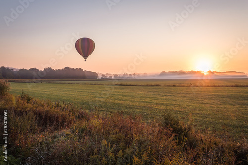 Tuinposter Ballon Hot air balloon lifts off over a farm field at sunrise, Pine Island, NY, early fall