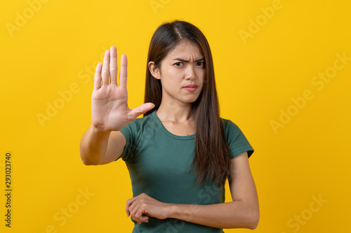 Fotografie, Tablou  Serious angry beauty asian teenager in green tee shirt showing hands to refuse something isolated on yellow background in studio
