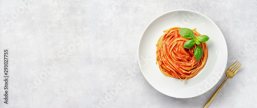 Photo Top view of plate eith pasta in tomato sauce and basil on white background