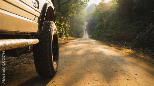 Part of an off-road vehicle on a dusty forest path with warm light.
