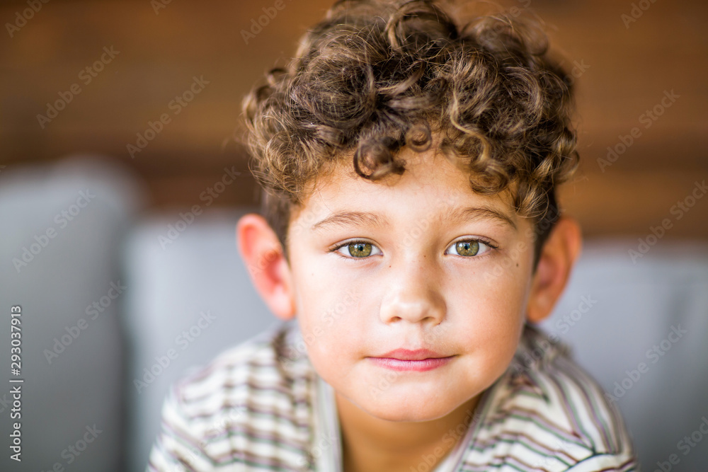 Fototapeta Handsome young boy with curly hair smiling.