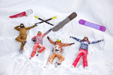 Happy friends having fun lying on snow aerial view. Ski and snowboard concept