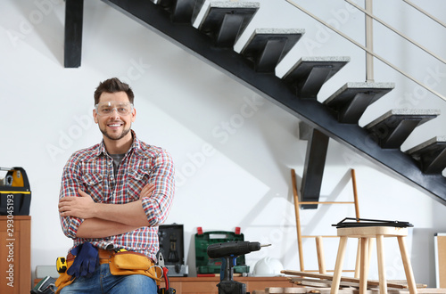 Obraz Handsome working man indoors, space for text. Home repair - fototapety do salonu