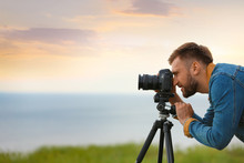 Male Photographer Taking Picture Of Beautiful Landscape With Professional Camera Outdoors. Space For Text