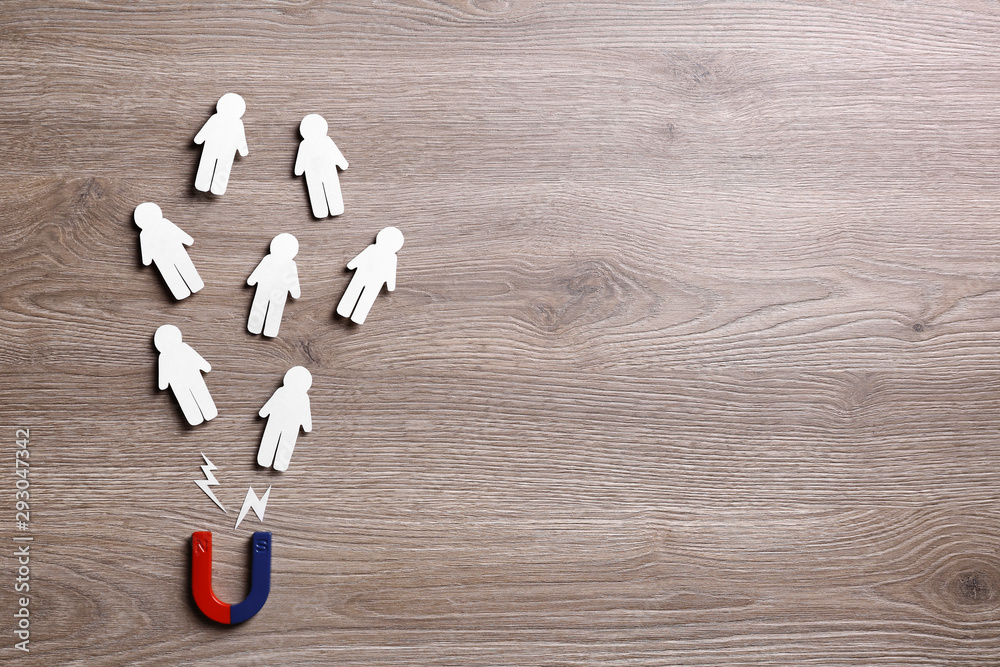 Fototapeta Magnet attracting paper people on wooden background, flat lay. Space for text