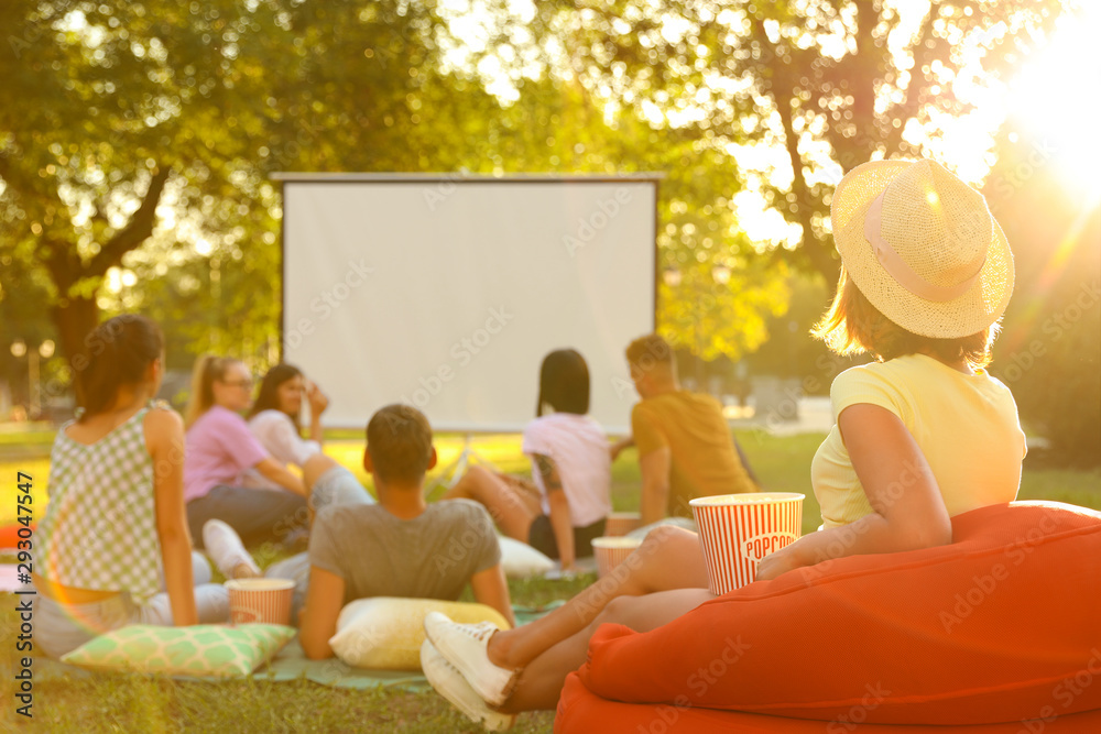 Fototapety, obrazy: Young people with popcorn watching movie in open air cinema. Space for text