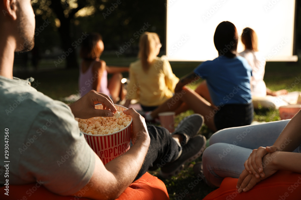 Fototapety, obrazy: Young people with popcorn watching movie in open air cinema, closeup. Space for text