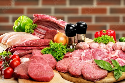 Fresh raw meat background with vegetables on wooden desk isolated on white background - 293048312