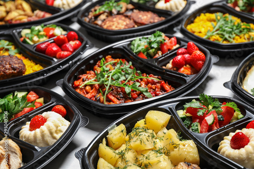 Lunchboxes with different meals on white table. Healthy food delivery