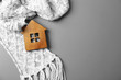 canvas print picture - Wooden house model and scarf on grey background, top view with space for text. Heating efficiency