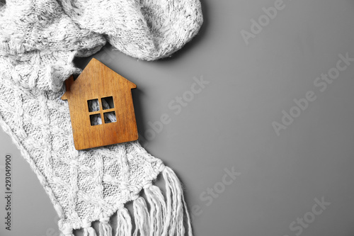 Vászonkép Wooden house model and scarf on grey background, top view with space for text