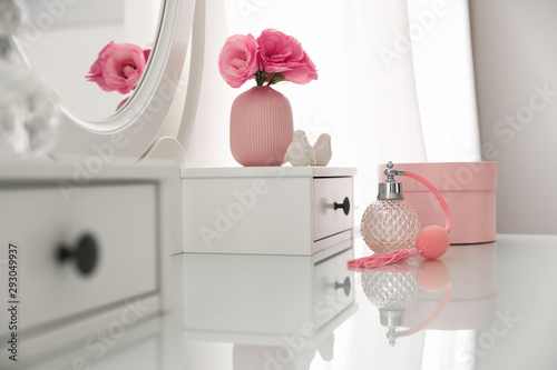 Fotografia White dressing table with decor and bottle of perfume in room
