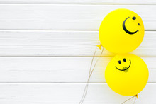 Happiness Emotion. Yellow Balloon With Smile On White Wooden Background Top View Space For Text