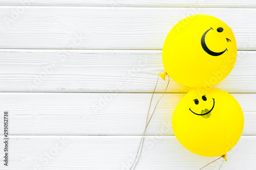 Obraz Happiness emotion. Yellow balloon with smile on white wooden background top view space for text - fototapety do salonu