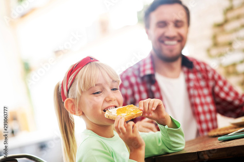 Foto Blonde girl eating yummy toast with egg for breakfast